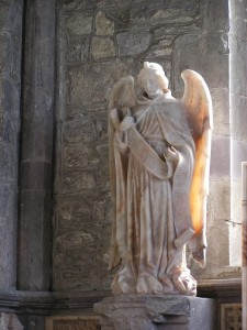 photo of a statue of an angel near a tomb in St. David's Cathedral, Wales, UK