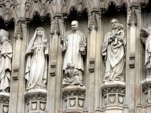 photo of statues of modern saints on pillars