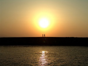 photo of two people walking along the shore backlit by the sun