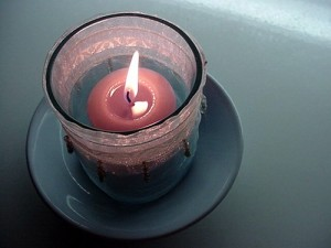 photo of a small, lit cup-candle